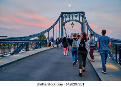 "Wilhelmshaven, Germany - June 14, 2019: people crossing the historic bridge ""Kaiser Wilhelm Brücke"" during dawn in front of bue-red sky"