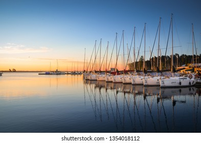 WILKASY, MASURIA , POLAND - AUGUST 12 2018: Boats docking in the marina at the Niegocin Lake during sunrise.