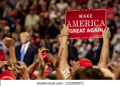 "WILKES-BARRE, PA - AUGUST 2, 2018: A fan holds up a ""Make America Great Again"" sign while President Donald J. Trump delivers a speech during the ""Make America Great Again"" rally at Mohegan Sun Arena."