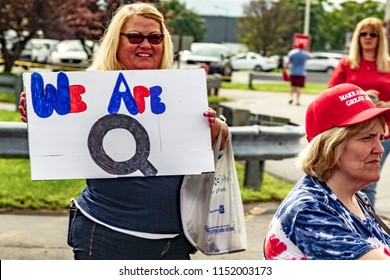 "WILKES-BARRE, PA - AUGUST 2, 2018: A woman holds a ""We Are Q"" sign while in line to attend the ""Make America Great Again"" rally held at the Mohegan Sun Arena. ""Q"" stands for QAnon, a conspiracy group."