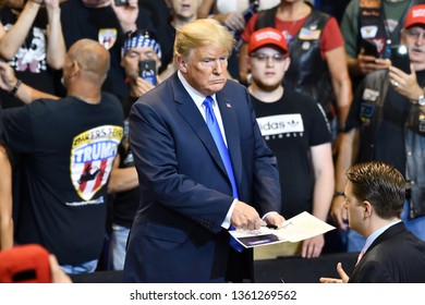 WILKES-BARRE, PA - AUGUST 2, 2018: President Donald Trump signs his autograph for a supporter at a campaign rally.