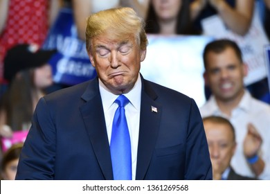 WILKES-BARRE, PA - AUGUST 2, 2018:  President Trump on stage reacts as he listens to congressman Lou Barletta speak to the crowd at his campaign rally.