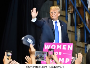 WILKES-BARRE, PA - AUGUST 2, 2018: President Donald Trump waves triumphantly to supporters as he leaves the stage at a campaign rally.