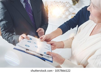 I will assist you. Positive elderly couple meetign with their insurance agent while holding folder and talking with him