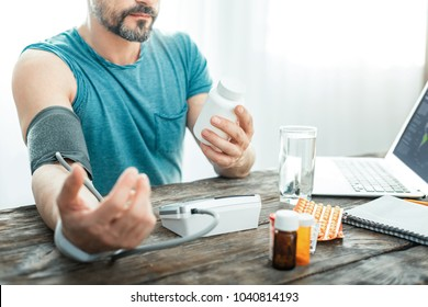 Will be better. Unshaken concentrated occupied man sitting by the table measuring pulse looking at the jar.