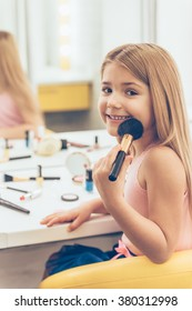 I will be ready in five minutes! Cheerful little girl applying make-up and looking at camera with smile whilesitting at the dressing table
