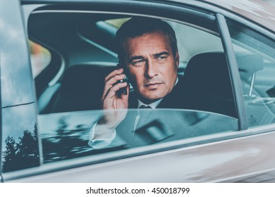 I will be in time. Confident mature businessman talking on the mobile phone and looking away while sitting on the back seat of a car