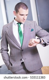 I will be in time. Handsome young man in formalwear looking at his watch while standing.