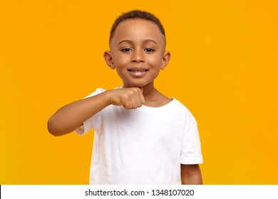I will cut your head off. Picture of positive cheerful dark skinned schoolboy having fun in yellow studio, making joke, holding thumb at his neck, showing menacing warning gesture, smiling broadly