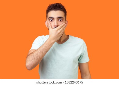 I will not say. Portrait of scared bullied man in white t-shirt covering mouth with hand, looking with frightened shocked eyes, keeping secret taboo. indoor studio shot isolated on orange background