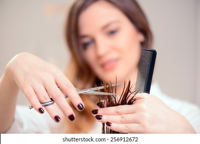 I will style you right. Selective focus image of beautiful hairdresser doing hairstyle to her client while standing on the background of a professional hairdressing salon