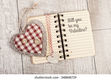 Will you be my Valentine Text in open lined notebook next to wooden-textile heart and book divider. Valentine day romantic greeting card design. This image is toned