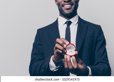 Will you marry me? Cropped close up photo of happy cheerful excited man dressed in smart suit holding a red box with engaging ting, isolated on grey background