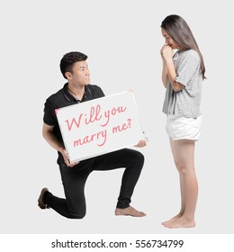 Will you marry me? Full length of man making proposal to his girlfriend while standing at his knee and showing a message board. Isolated on grey background