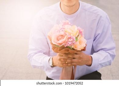 Will you marry me. A guy knees down with a bouquet of flowers in his hand proposing.