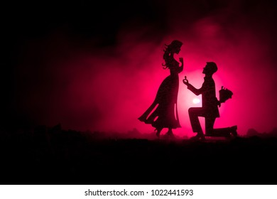 Will you marry me? Silhouette of young man staying on the knee and making proposal for his lovely girl against dark toned background. Valentine greeting card decor. Selective focus