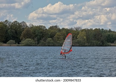 WILLEBROEK, BELGIUM, MAY 2, 2021, Wind surfer on a lake with forest on the embankment on a cloudy spring day in Willebroek, 2 May 2021
