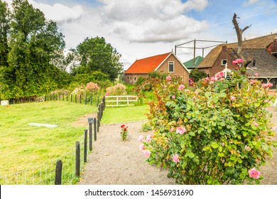 Willem van der Veldenweg 47, Leimuiden, Municipality, Kaag and Braassem, Zuid Holland, the Netherlands, July 9, 2019: Old monumental farmstead in South Holland landscape with farmers flower garden