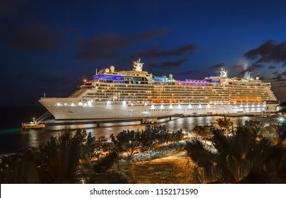 WILLEMSTAD, CURACAO - APRIL 11, 2018:  Cruise ship Celebrity Equinox docked at night in port Willemstad. The island is a popular Caribbean cruise destination