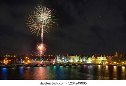 Willemstad, Curacao - April 12, 2018: Fireworks at Willemstad with the famous old colonial facades and Illuminated Queen Emma Bridge