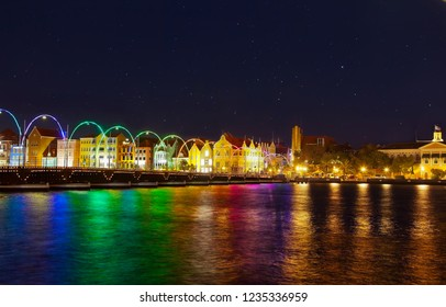 Willemstad, Curacao - April 12, 2018: Willemstad by night with the famous old colonial facades and Illuminated Queen Emma Bridge