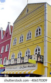 WILLEMSTAD, CURACAO - CIRCA JULY 2014: Brightly colored shops on the main street leading to the swinging bridge