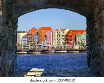 Willemstad, Curacao - JANUARY 15, 2019: View through old arch to Specific colored buildings on Handelskade street in Curacao.