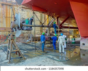 Willemstad, Curacao/ Netherlands Antilles - April 15 2009: Shipyard workers use a crane & chain blocks to draw the tail-shaft and propeller from a small passenger ship for maintenance.
