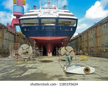 Willemstad, Curacao/ Netherlands Antilles - April 19 2011: A shipyard worker paints the rudder, which has been removed to facilitate the drawing of the tail-shafts & propellers.