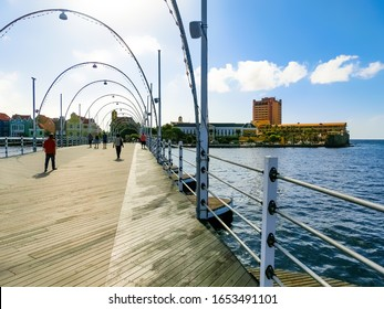 Willemstad, Curacao, Netherlands - December 5, 2019: People at Queen Emma Bridge in front of the Punda district, is a pontoon bridge across St. Anna Bay at Willemstad, Curacao, Netherlands on December
