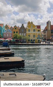 WILLEMSTAD, CURACAO - NOVEMBER 22, 2007: The pontoons of the Queen Emma Bridge opens in the towncentre of Willemstad with the colorful houses at the Handelskade in the background.