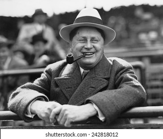 William Wrigley, (1861-1932), president of chewing gum company, watching a game between his Chicago Cubs and the St. Louis Cardinals, in Chicago, Illinois. Ca. 1925.