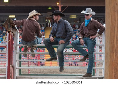 Williams Lake, British Columbia/Canada - July 1, 2016: three cowboys sit on the chutes and watch the 90th Williams Lake Stampede, one of the largest stampedes in  North America