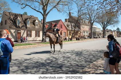 Williamsburg, VA- United States- 03-29-2021: A costumed actor from the Colonial period entertains tourists along Duke of Gloucester Street.