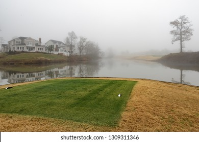 Williamsburg, Virginia - December 15, 2018: Tee box on the water of a lake with mansion houses overlooking on a professional PGA golf course at Kingsmill Resort.