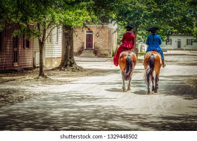 Williamsburg, Virginia / United States – June 30, 2016: Two Colonial Williamsburg residents on a horseback stroll.