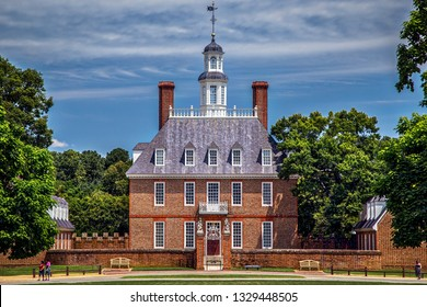 Williamsburg, Virginia / United States – June 30, 2016: Unidentified tourists pass by the Colonial Williamsburg Governor's Palace.