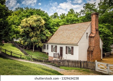 Williamsburg, Virginia / United States – June 30, 2016:  A small house sits in a meadow at Colonial Williamsburg.