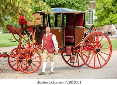 Williamsburg, Virginia, USA - 6/23/2009: A coachman dressed in period clothing is standing by his coach in colonial Williamsburg.