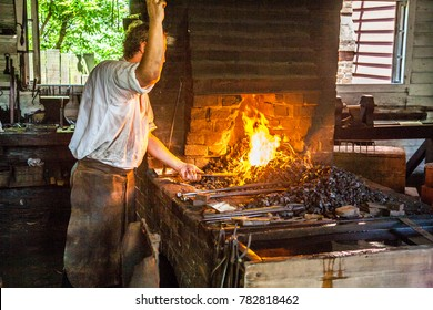 Williamsburg, Virginia, USA - 6/23/2009: A man dressed in period clothing is demonstrating blacksmith activities in colonial Williamsburg.