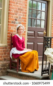 Williamsburg, Virginia, USA - 6/23/2009: A woman dressed in period clothing is sitting in front of the millinery shop in colonial Williamsburg.