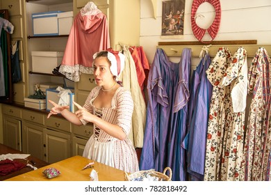 Williamsburg, Virginia, USA - 6/23/2009: A woman dressed in period clothing is telling about activities in a millinery shop in colonial Williamsburg.