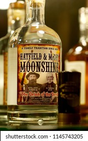 """Williamson, West Virginia, USA - July 23, 2018: Close-up of a bottle of """"Hatfield & McCoy Moonshine"""" on display at the Mountaineer Hotel in Mingo County where the infamous family feud took place."""