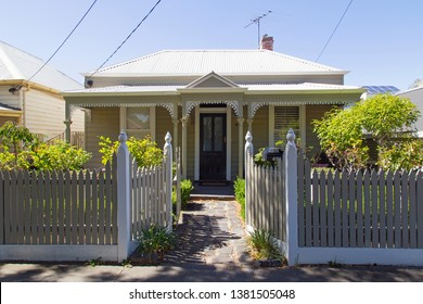 Williamstown, Australia: March 07, 2019: Traditionally built bungalow in the 20th century Australian style in Williamstown with a porch, ornate verandah, garden path, and painted picket fence.