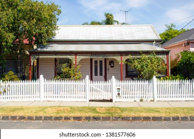 Williamstown, Australia: March 07, 2019: Traditionally built detached bungalow in the 20th century Australian style with a porch, ornate verandah, garden path, and white painted picket fence.