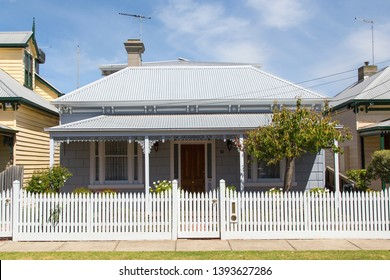 Williamstown, Australia: March 07, 2019: Traditionally built bungalow in the 20th century Australian style in Williamstown with a porch, ornate verandah, garden path, and white picket fence.