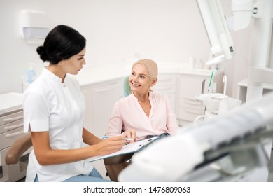 Willing to know. Cheerful patient asking her dentist sitting next to her filling up her form about her procedures.