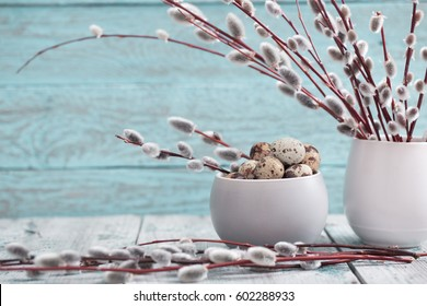 Willow branches and quail eggs on a wooden background