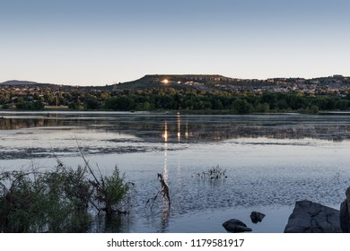 Willow creek lake in Prescott Arizona. sunlight reflecting off several house windows across the lake. window reflections reflecting off the lake water. water plants and rock boulders in the foreground
