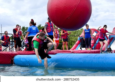 "Wilmington, Delaware, USA - June 13, 2015: Friends running at the ""wrecking balls"" water obstacle at the Wipeout 5K Run obstacles course in Wilmington Delaware on June 13, 2015"